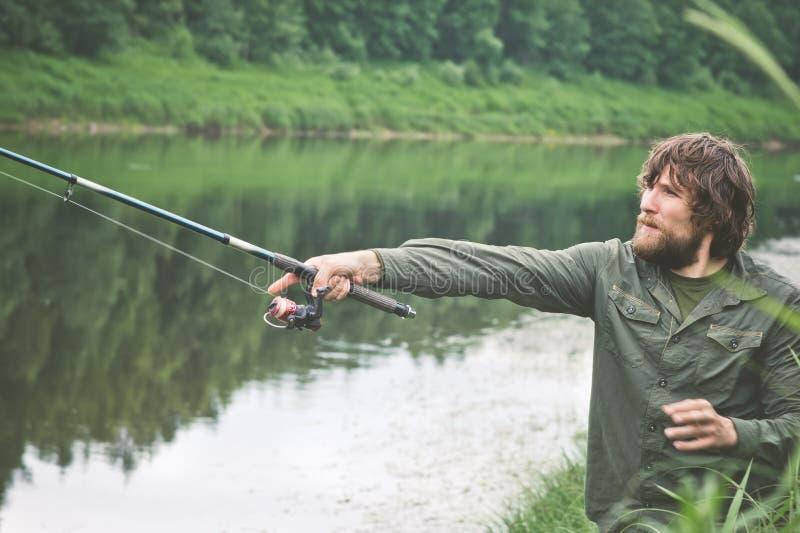 Pêche barbue de pêcheur de jeune homme avec la tige images stock