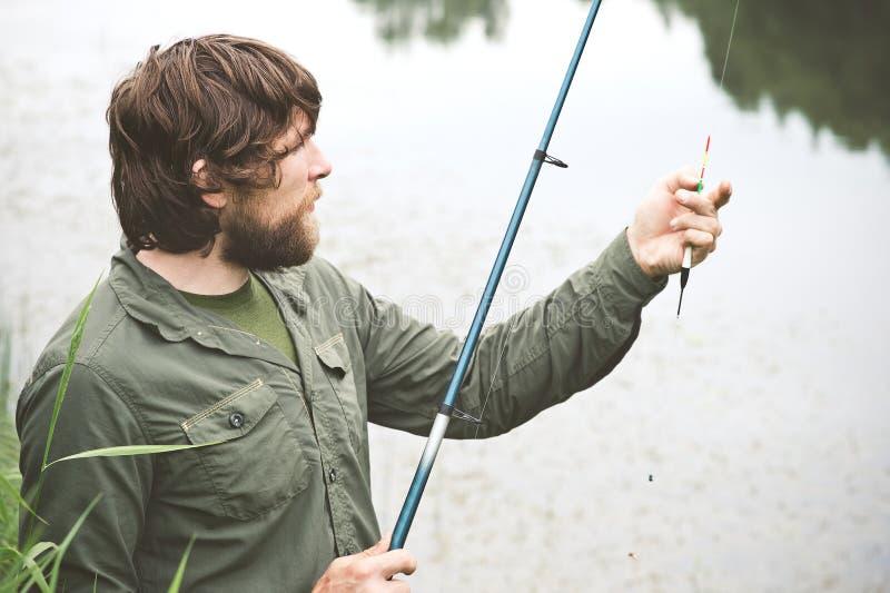 Pêche barbue de pêcheur de jeune homme avec la tige image stock