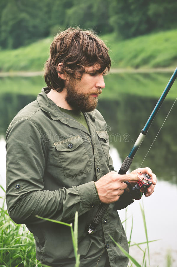 Pêche barbue de pêcheur de jeune homme avec la tige image libre de droits