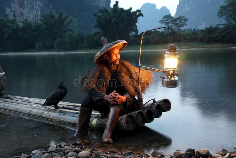 Pêche chinoise d'homme avec des oiseaux de cormorans dedans photographie stock libre de droits