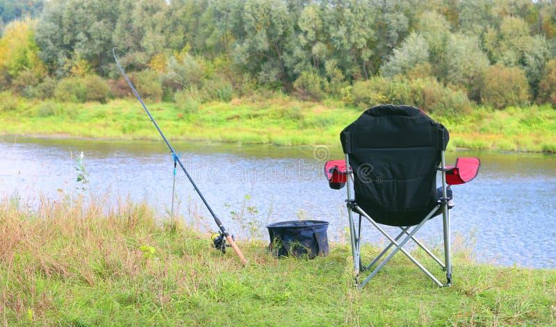 Pêche d'été avec une tige et chaise de touristes se pliante confortable sur la berge parmi l'herbe verte et les beaux arbres images libres de droits