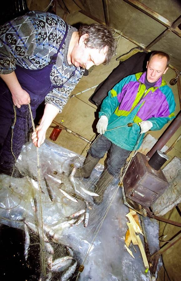 Pêche d'hiver sur la glace de Baikal Des pêcheurs sont employés dans la pêche d'hiver image libre de droits