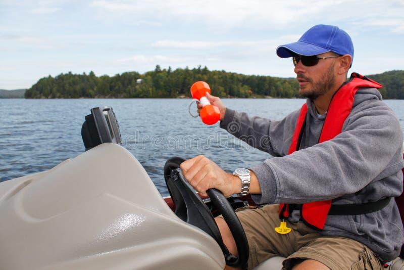 Pêche d'homme dans la balise et le sonar de marqueur de bateau photographie stock