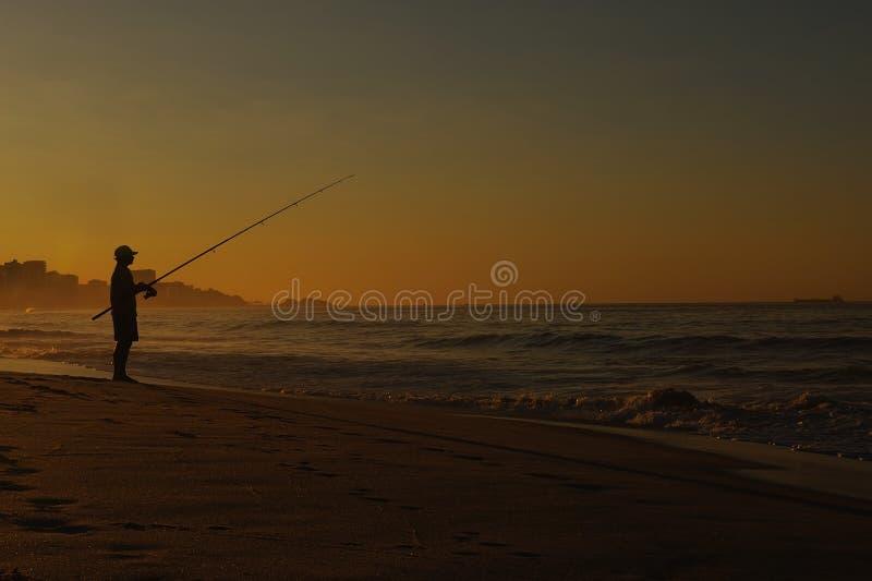 Pêche d'homme de silhouette sur la plage images stock