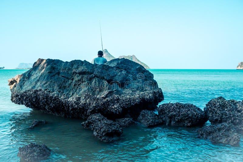 P?che d'homme sur des roches parmi l'id?e bleue d'?t? de vacances d'oc?an images stock