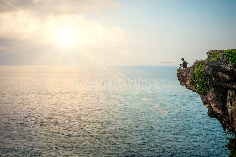 Pêche d'homme sur le bord de la falaise sur la côte indienne photos libres de droits