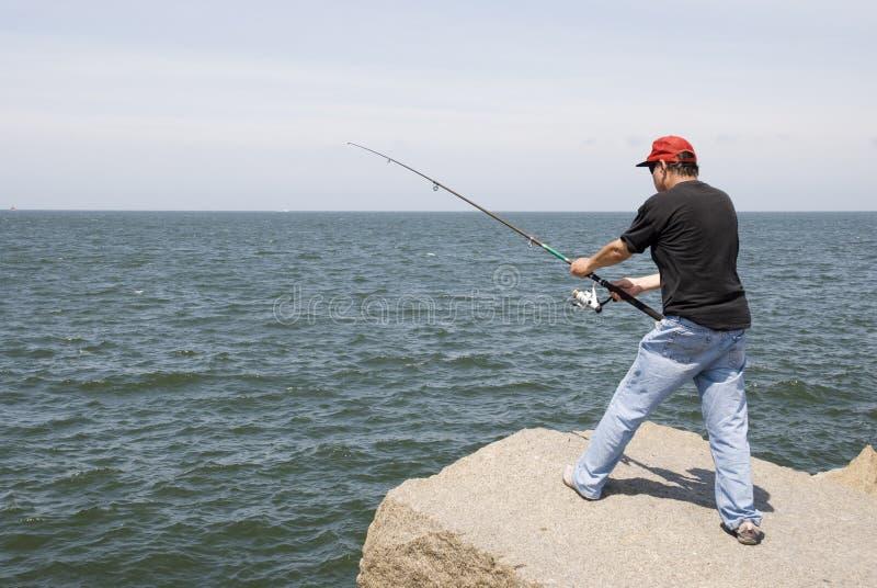 Pêche d'homme sur une roche photos libres de droits
