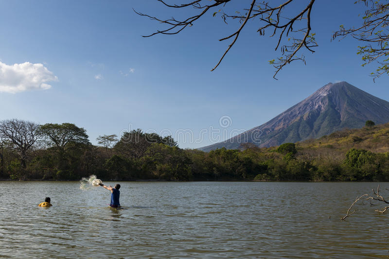 Pêche de deux pêcheurs dans les rivages de l'île d'Ometepe dans le lac Nicaragua, avec le volcan de Concepcion sur le fond photographie stock libre de droits