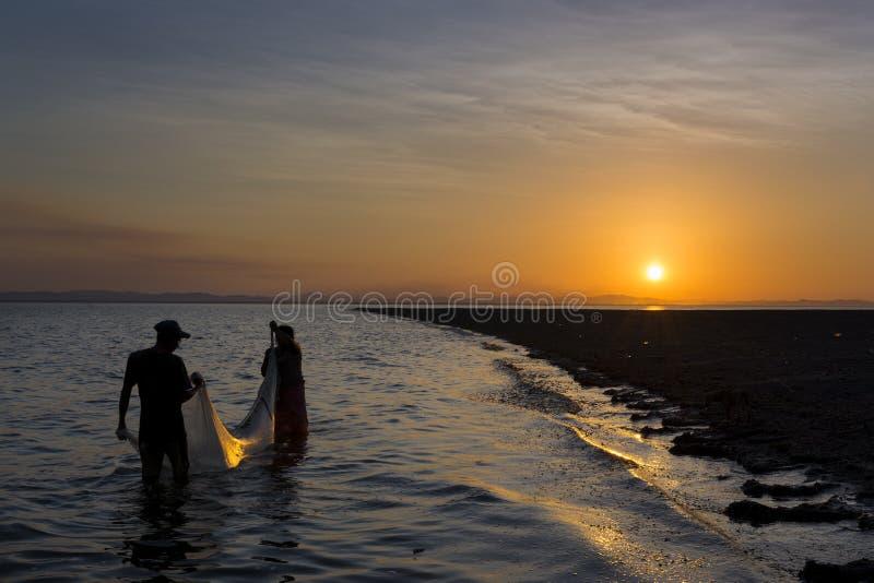 Pêche de deux pêcheurs dans les rivages de l'île d'Ometepe dans le lac Nicaragua, Nicaragua, au coucher du soleil images stock