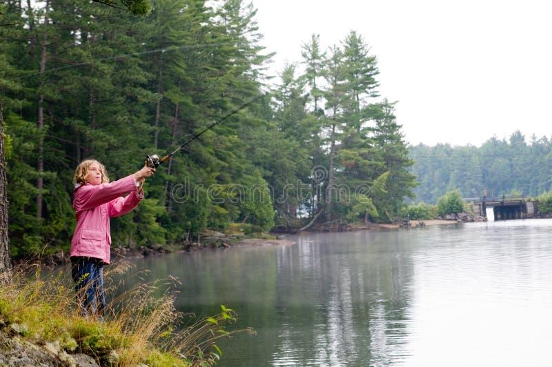 Pêche de fille sur le côté d'un lac image stock