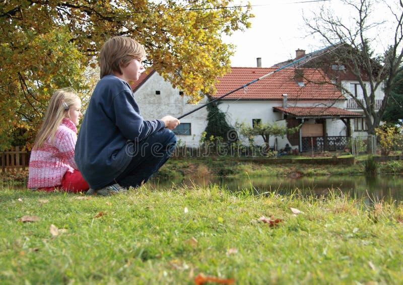 Pêche de garçon et de fille sur l'étang photos stock