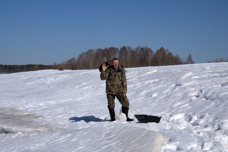 Pêche de glace d'hiver, un pêcheur dans des vêtements chauds pêchant dans le trou - Russie Berezniki le 7 avril 2018 photos libres de droits