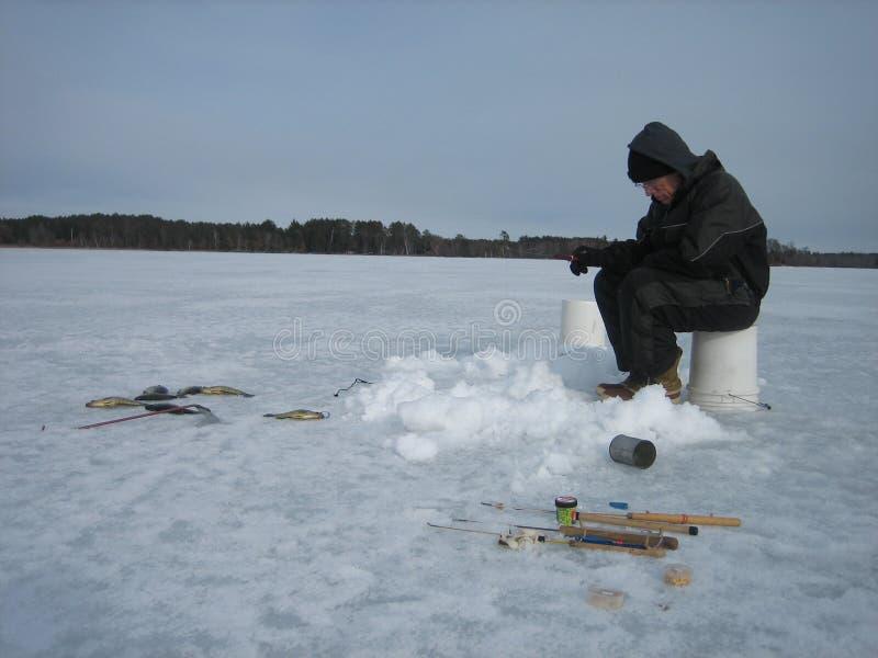 Pêche de glace sur un lac congelé photographie stock libre de droits