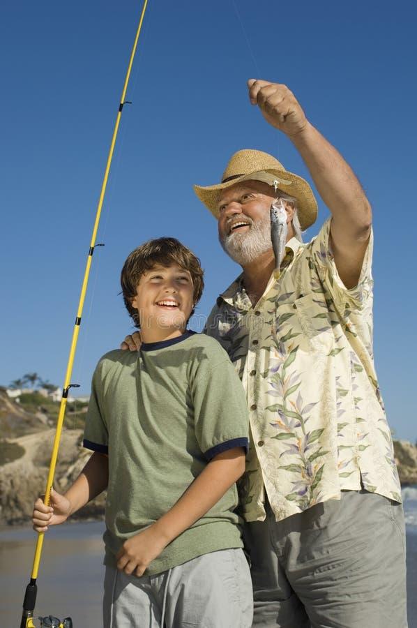 Pêche de grand-père et de petit-fils sur la plage photo libre de droits