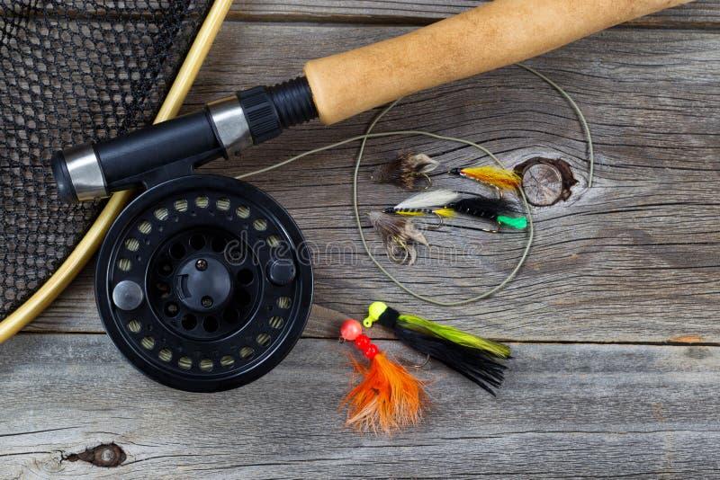 Pêche de la bobine de mouche avec des accessoires sur le bois photographie stock