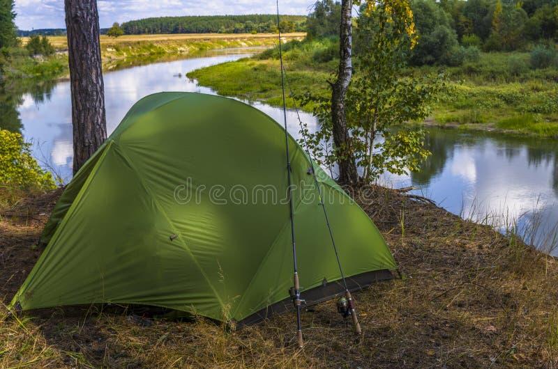 P?che de la tente de camping sur le rivage de rivi?re Voyage, loisirs et tourisme en nature photographie stock libre de droits