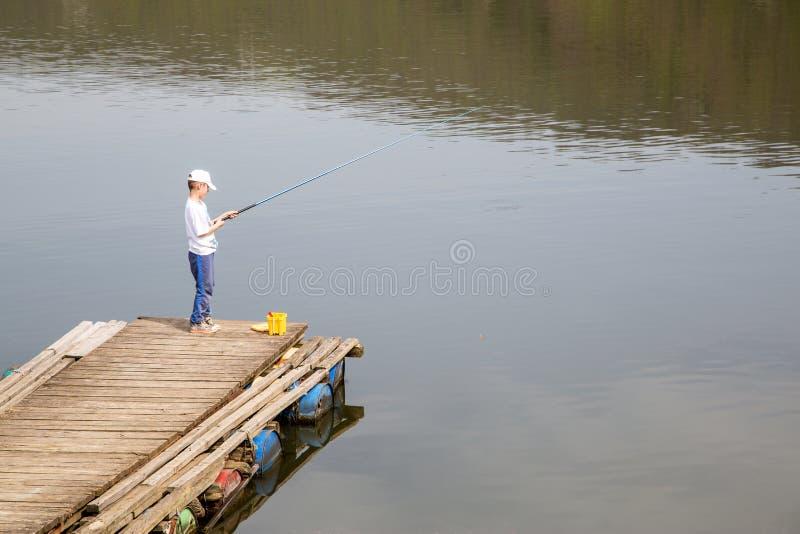 Pêche de Little Boy sur les poissons de attente de lac pour prendre une amorce ayant l'amusement des vacances d'été images libres de droits
