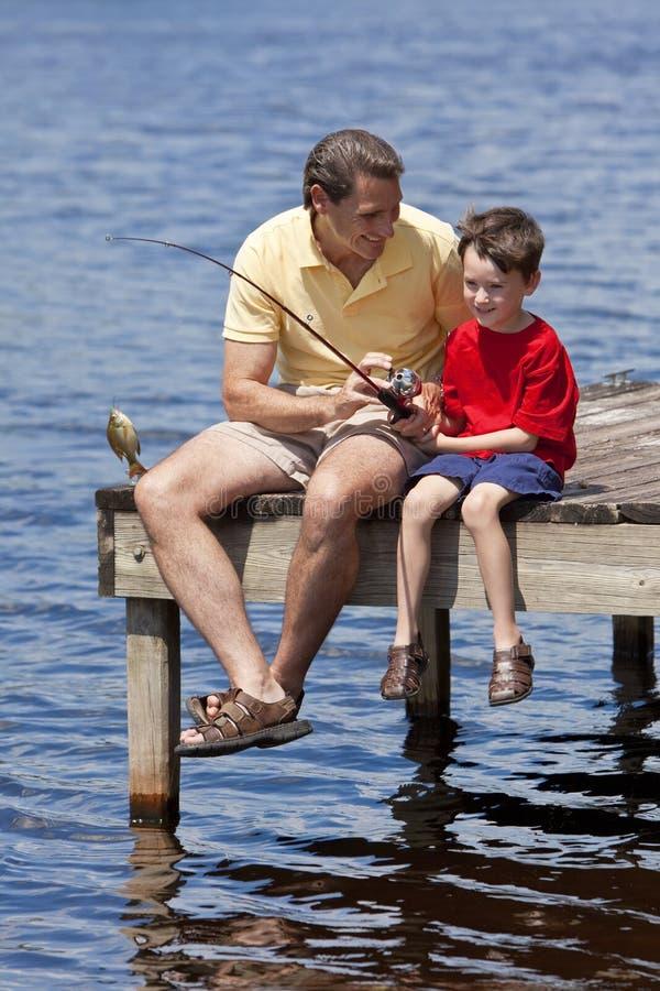 Pêche de père avec son fils sur une jetée photo stock