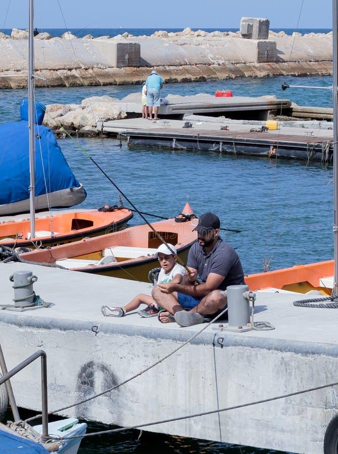 Pêche de père et de fils sur le bord de mer dans Yafo, Israël photographie stock
