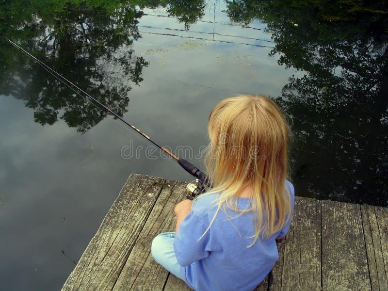 Pêche de petite fille d'un dock photographie stock libre de droits