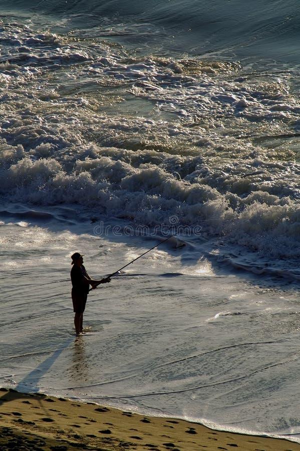 Pêche de vague déferlante d'homme dans l'océan images libres de droits