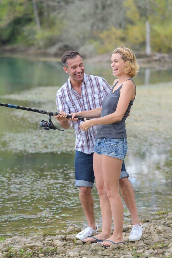 Pêche heureuse de couples par l'étang photographie stock