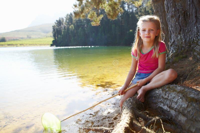 Pêche heureuse de fille au lac image stock