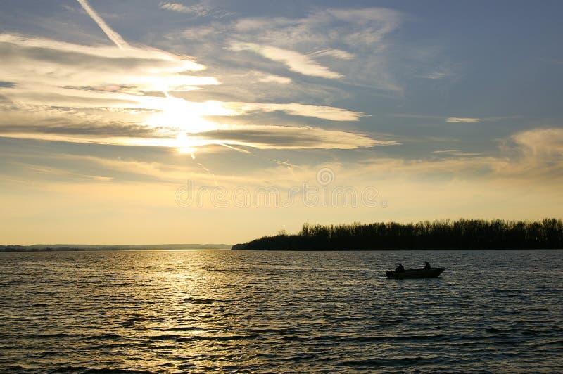Pêche sur le lac avec le coucher du soleil scénique image stock