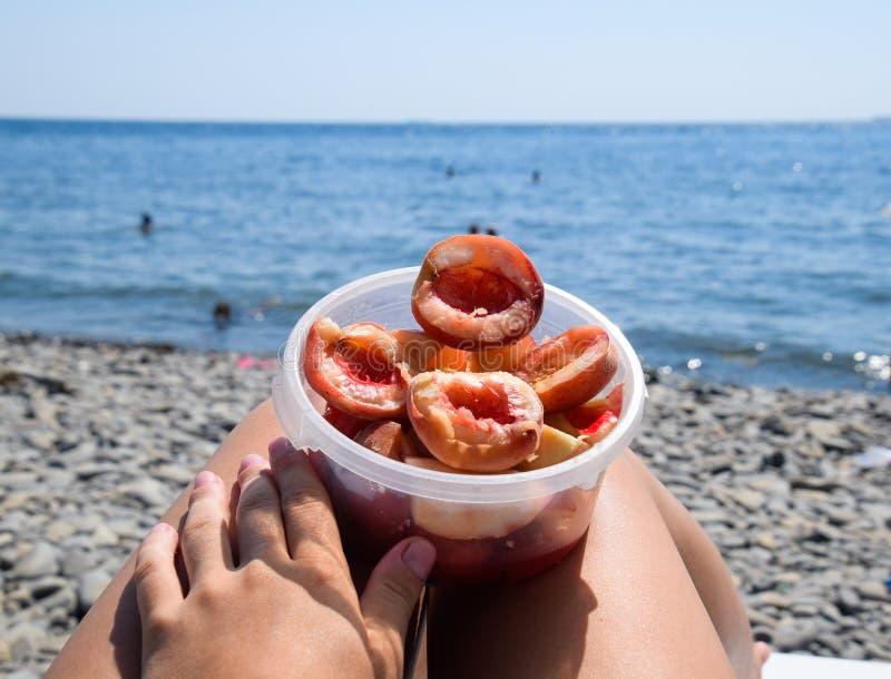 Pêches épluchées dans une tasse sur les jambes femelles Vacances de plage par la mer photos stock