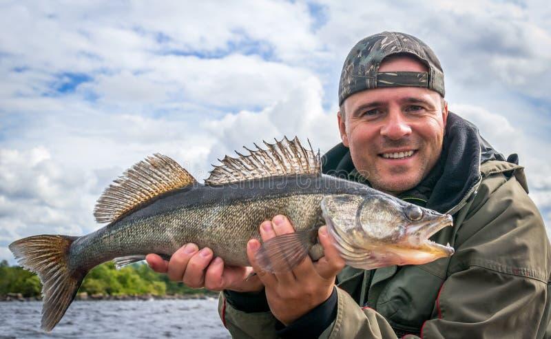 Pêcheur à la ligne avec le trophée de pêche de zander photographie stock libre de droits