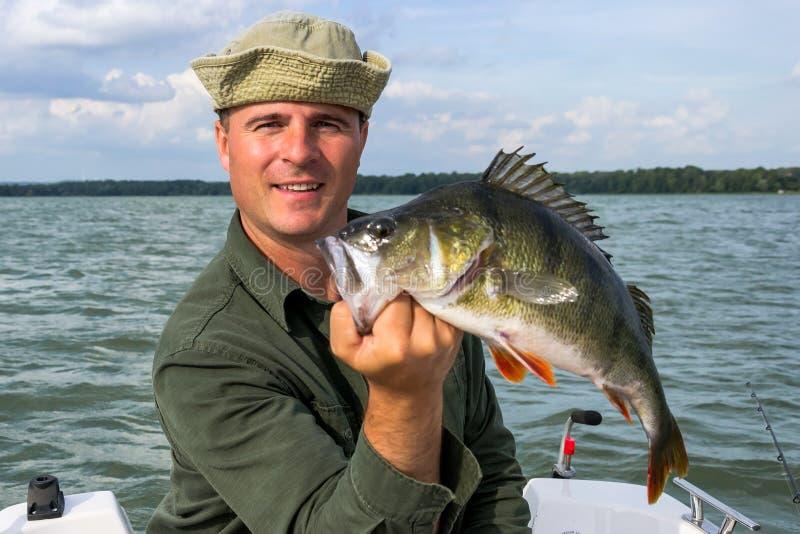 Pêcheur à la ligne avec les poissons énormes record de perche images libres de droits
