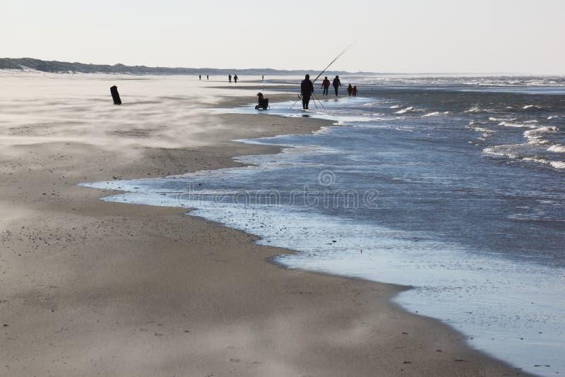 Pêcheur à la ligne et marcheurs sur la plage dans Nes, Ameland, Hollande photographie stock