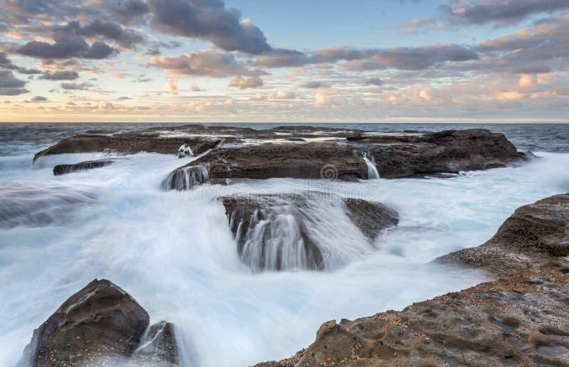Pêcheur échoué de roche presque pris par l'océan photographie stock libre de droits
