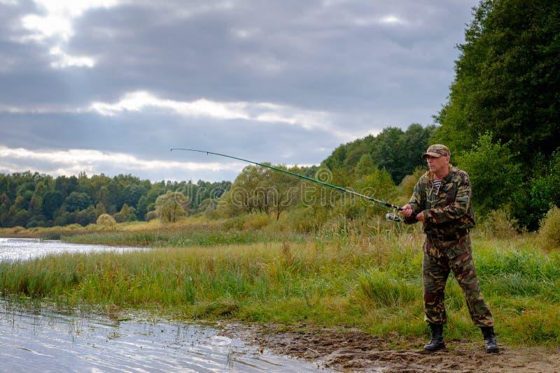 Pêcheur avec la pêche de tige photos stock