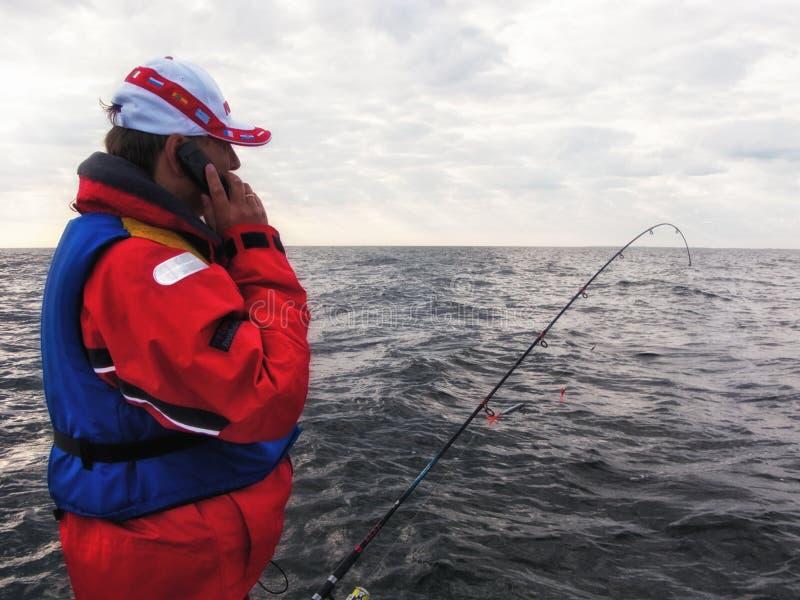 Pêcheur avec le téléphone portable images stock