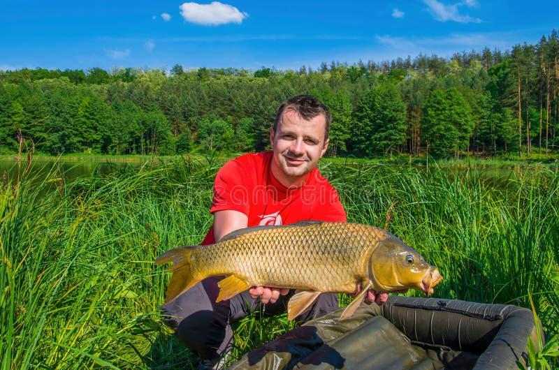 Pêcheur avec le trophée de pêche de carpe photo libre de droits