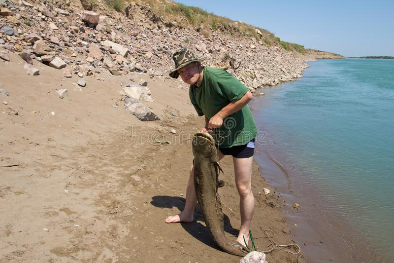 Pêcheur avec un grand poisson-chat image stock
