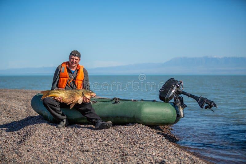 Pêcheur chanceux tenant un beau poisson de trophée photographie stock libre de droits