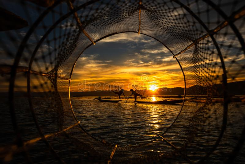 Pêcheur d'Intha posant avec les filets coniques au coucher du soleil, lac Inle dans la pièce de banlieue noire de Nyaungshwe de S photos stock