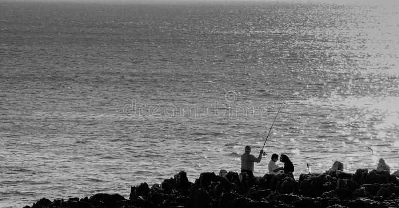 Pêcheur dans les roches, Cascais images stock