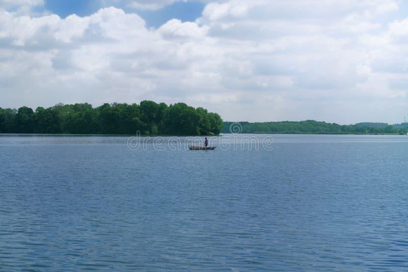 Pêcheur dans un bateau au milieu d'un lac photo libre de droits