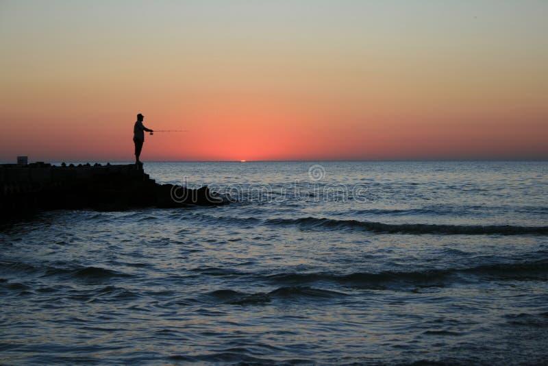 Pêcheur de coucher du soleil photo stock