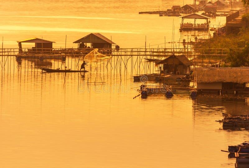 Pêcheur de silhouette moulant les poissons nets de crochet pendant la position sur le bateau en bois le temps de coucher du solei image stock