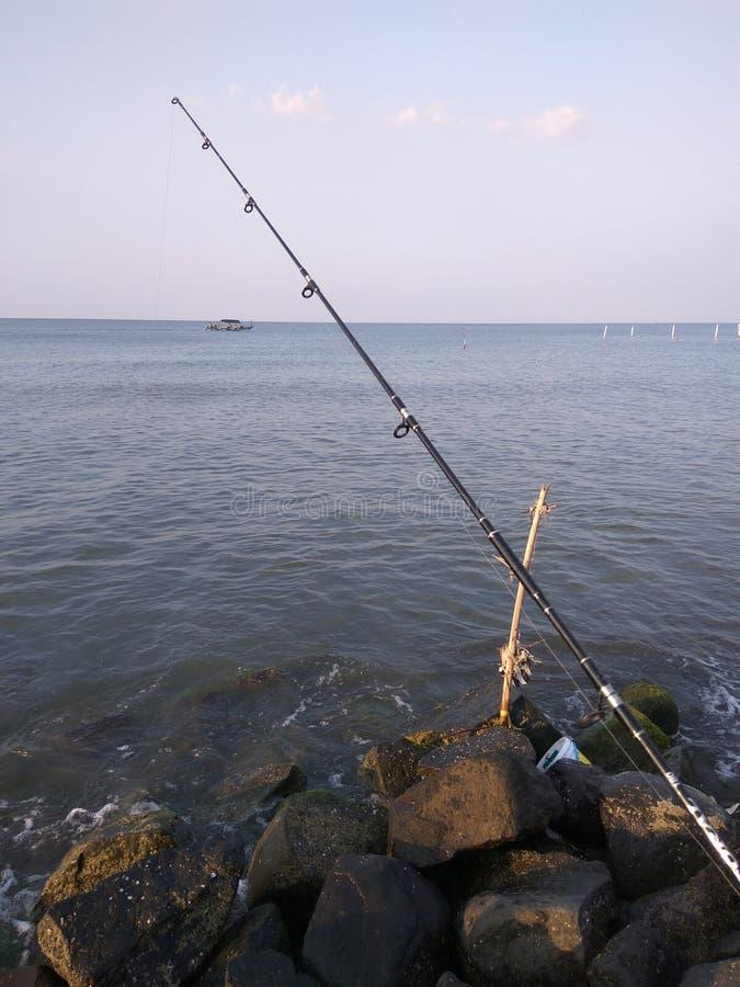 Pêcheur de temps de pêche? dans le lac, près de au coucher du soleil photographie stock libre de droits