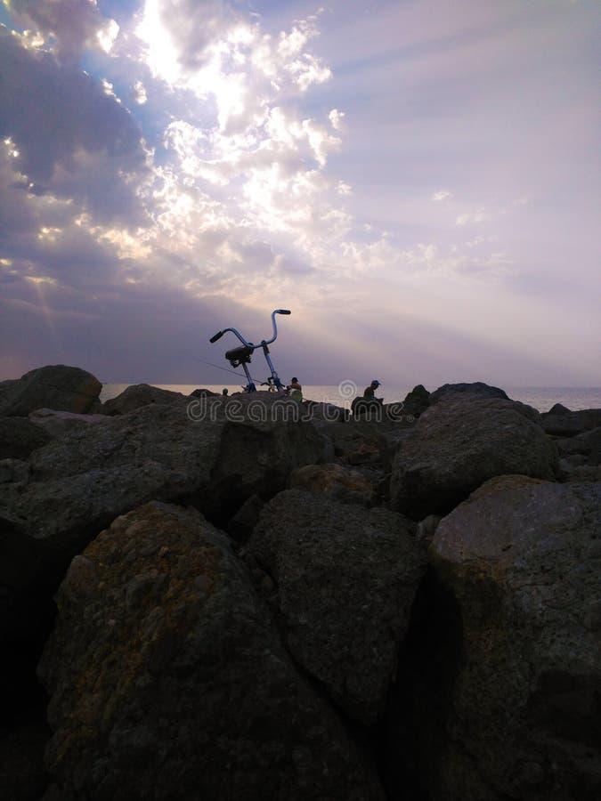 Pêcheur de vélo qui est venu à la pêche sur le fond d'un beau coucher du soleil image libre de droits