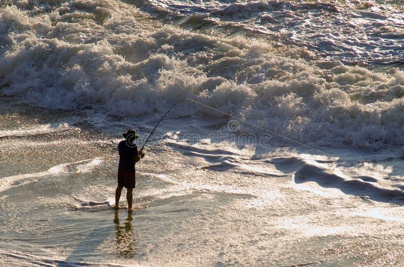 Pêcheur de vague déferlante photo stock