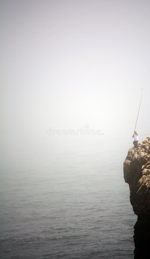Pêcheur en falaise photographie stock