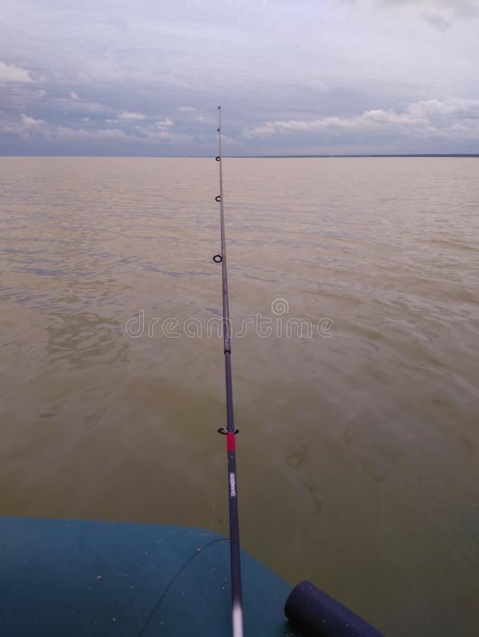 Pêcheur enthousiaste de canne à pêche, abandonné dans l'eau en prévision des morsures image stock