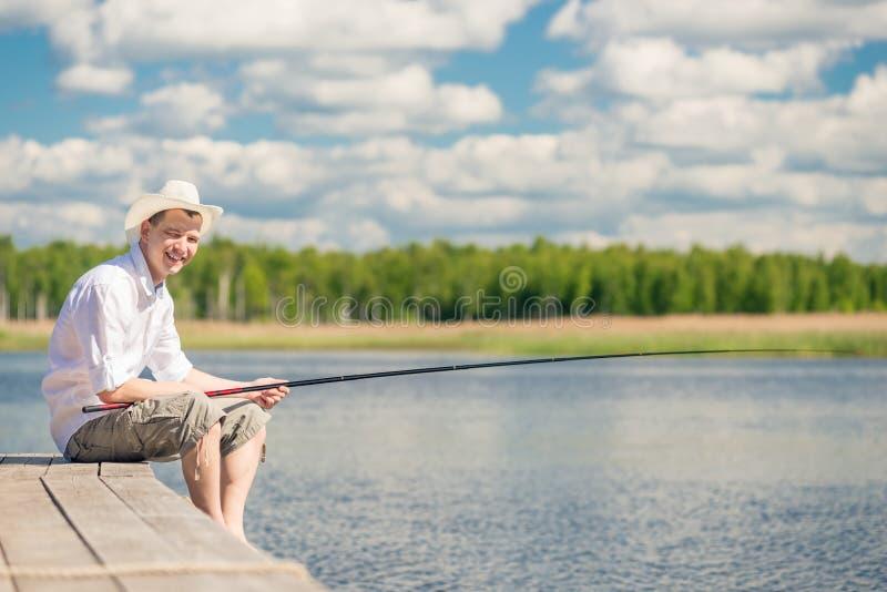 Pêcheur heureux dans un chapeau sur un pilier en bois sur de beaux WI d'un lac photographie stock
