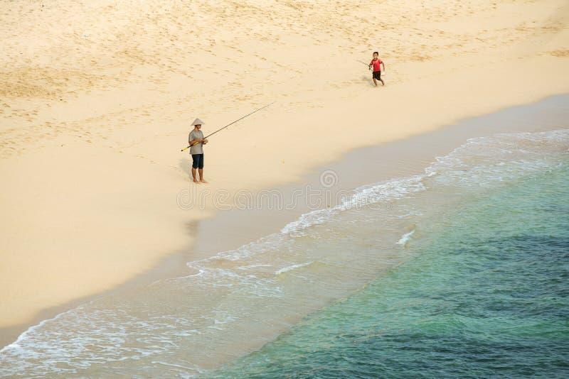 Pêcheur inconnu avec un garçon avec la canne à pêche sur la plage photographie stock